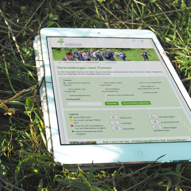 Ansicht der Website der Biologischen Station Zwillbrock auf einem Tablet auf der Wiese liegend.